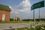 This sign, seen from southbound Ind.-105 alerting drivers to Bracken's presence, is part of what little is left of the agricultural community of Bracken. The former Warren Township District School 2, a one-room schoolhouse, can be seen on the left.