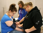 HNHS senior Marissa Brown (left) offers her arms for a bilateral blood pressure check, taken by fellow health occupations/medical terminology students Lauren Sands (center) and Amanda Muench (right). Following the class the students can choose to go into certified nursing assistant or emergency medical technician training through the high school's vocational tech program.