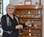 Dee Kochensparger shows off some of the miniature oil lamps she has collected. The lamps are now on display at the Andrews-Dallas Township Public Library.