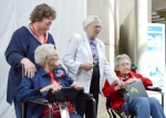 Honor Flight Northeast Indiana Founder Laura Carrico (standing at left) assists World War II United States Navy veteran June Harshman (seated at left) as retired Air Force Brigadier General Wilma Vaught (standing at right) helps WWII Army veteran Polly Lipscomb during a past Honor Flight to Washington, DC. Carrico will be recognized during the upcoming 20th flight planned for Wednesday, May 25.