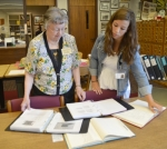 Library staff members Diane Miller (left) and Amber Hudson pore over the books that Marsha Martin has contributed to the Huntington City-Township Public Library's Indiana Room on Monday, July 11. Martin has written 12 books on the cemeteries in Huntington County that are available in the Indiana Room.