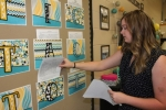 Lancaster Elementary School fourth-grade teacher Kayla Whitacre works on a bulletin board offering tasks for her students that can earn them extra credit or prizes in her classroom on Thursday, Aug. 3. School begins for students on Wednesday, Aug. 9.