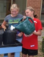 Flint Springs Elementary School fifth-graders Kayla Ables (left) and Ashlynn Snyder water newly planted vegetable seeds in the school's courtyard garden on Tuesday, Aug. 25.