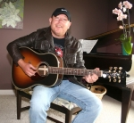 """Allan Craig Miller strums a tune on guitar in his home in rural Huntington County. The Huntington native is planning a concert tour in Europe, after his song """"Between Saturday & Sunday"""" debuted at No. 3 on the European country music charts and rose to No. 2."""