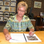 Jody Davenport, president of the Huntington Area Recreational Trails Association (HARTA), studies a report compiled by Indiana University urban planning students concerning rails expansion in Huntington County.