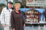 Tom and Sharon Laupp, of Andrews, stand in front of their Christmas Spirit dollhouse on Monday, Dec. 1. The decorated dollhouse is part of the Crop Production Services Christmas display in the window of D&D Bike Shop in Warren. The display won first place in the business division of the town's window decorating contest.