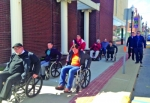 Huntington Mayor Brooks Fetters (far left) leads the charge for the Mayor's Downtown Roll-Around, as a cavalcade of wheelchair-bound officials and others makes their way along a downtown street in observance of Disability Awareness Month in March. The annual trip, which will return this year on March 28, is an exercise in getting a feel of the challenges some disabled people face in navigating simple everyday ambulatory tasks.