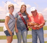 Sarah Jones (middle), of Warren, was named the 2017 Indiana Duroc queen. Jones' grandfather, Guy Jackson (right), holding a Duroc piglet, passed a love of pigs on to his family, which inspired Jones' mother, Kelly Jones (left), to become Duroc queen, as well as her aunt, Karen Johnson, and sister, Suzzette Corbin.