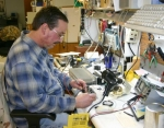Carl Draper, one of the founders of Electrical Mechanical Devices, Inc., tests a computer board at the EMD office on Monday, Feb. 15. EMD repairs a variety of electronics at its Huntington location.