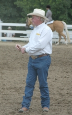 Ring steward Bob Jones sends a signal to the announcer to ask riders to change their pace during the Huntington County 4-H Horse and Pony Show Sunday, July 19, at the Chief LaFontaine Saddle Club.
