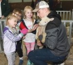 Huntington North High School FFA member Ty Miller (right) holds a newborn lamb so kindergarteners (from left) Cadence Smith, Colten Latta and Alexis Wine can pet it during the annual kindergarten farm tour on Friday, May 3, at the Carriage Lane Farm. The kids learned lessons from the FFA members about where their food and other products come from, such as wool for clothing.