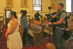 "Gabrielle Carreon (left), who plays Alondra Martinez in the film ""Polaroid,"" is filmed by Huntington University student T.J. Clounie, as Professor Lance Clark watches the monitor over his shoulder. SS. Peter and Paul Catholic Church served as a movie set for the day on Friday, March 20, as HU film production students spent their spring break shooting the movie."
