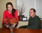 Kayla Godfroy Norman arranges a fall bouquet of flowers on her dining room table as her husband, Andy Norman, looks on. The couple is celebrating their Native American roots during Native American Heritage month.