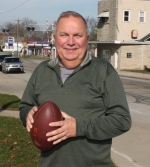 Andrews Clerk-Treasurer Bill Johnson hangs on to a football outside of Andrews Town Hall on Wednesday, Nov. 25. Johnson attends high school football games all over the state of Indiana to satisfy what he calls an addiction to the sport.