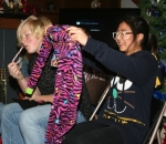 "Huntington North High School exchange student Kara Laohawee (right), from Thailand, holds up some warm footie pajamas she received as a Christmas present from her host family during a family Christmas exchange Saturday, Dec. 20. Her host family ""sister,"" Kloee Vickrey, sits next to her. About 20 people gathered at the home to have dinner and open presents."