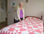 "Marjorie Gard shows off the quilt she made 85 years ago, as a 17-year-old girl, and that she still uses as a bedcover. The pristine-looking quilt caught the attention of visitors to the Salamonie Summer Festival, who voted to give it the ""People's Choice"" honor."