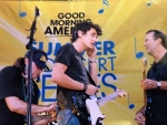 """Huntington native and audio technician John Gernand (left) applies a microphone to musician John Mayer (middle) while musician Eric Clapton looks on prior to a concert on """"Good Morning America"""" in New York City's Bryant Park in 2007. Since 1979, Gernand has lived in the Big Apple, where he works professionally in audio."""