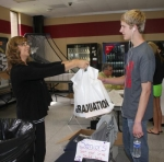 Sue Muncy of Jostens hands a bag of graduation goodies to senior Thomas Bolinger during lunch at Huntington North High School on Monday, April 21.