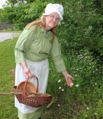 Salamonie Lake Interpretive Naturalist Laura Whiteleather, as Millie the pioneer granny doctor, forages for some plants to add to her basket of wild herbs used to treat illnesses and maladies such as poison ivy. Whiteleather has been giving her presentation for the past nine years.