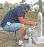 "John ""Walt"" Walters fills a large crack in a repaired tombstone at an abandoned cemetery in Roanoke on Wednesday, Oct. 13."