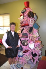Stephenie Murchland, owner of Village Salon, in Markle, stands in her shop next to a pink Christmas tree filled with vintage hats.