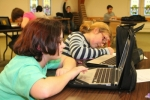 Isis Glover, 12 (left), a student at Riverview Middle School, and Katie Brown, 11, a student at Crestview Middle School, use their laptop computers to work on their homework at the Homework Help program at St. Peter's First Community Church. An average of 20 middle and high school students attend the session each day to complete their homework assignments, and get help if necessary.