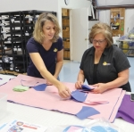 Magne Shade Production Manager Shirley Elling (left) works with owner Clare Hunckler to sort cut-out pieces of the facemasks the company has been making for healthcare workers.