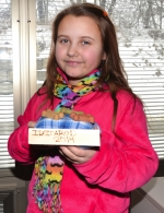 Jada Tucker, a fourth-grader at Lincoln Elementary School, displays one of the centerpieces she and her classmates made for the Feb. 27 Mushers' Drawing Banquet in Anchorage, AK.