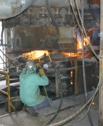 Tom Converse, of Peru, and formerly of Huntington, releases molten iron in one of the blast furnaces at the Isolatek International plant in Huntington on Thursday, May 20.