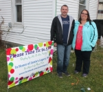 Chad (left) and Danielle Waters stand outside their home at 1220 Superior St., Huntington, where they have created a computer-programmed light show. The display is in honor of Jamie's Legacy, an organization which traps, spay/neuters and releases feral cats.