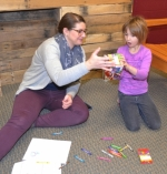 Kids Hope USA volunteer Sarah Wust (left) and Flint Springs Elementary School first-grader Elyni Long check out a boxed puzzle they planned to do during their meeting on Tuesday, Jan. 31, at Flint Springs.