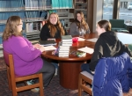 """Brianna Smith and Rebekah Smith (second and third from left, respectively), members of the Teen Book Club at the Huntington City-Township Public Library, discuss the club's latest selection, """"The False Prince"""" by Jennifer A. Nielsen, with club leader Jessi Brown (far left) and fellow member Jessica Hartmus on Thursday, Feb. 19. The club is one of many ways the library reaches out to teens, which can be a challenging demographic to attract."""