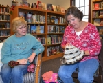 Edna Strickler (left) admires a crocheted hat made by Linda Clark. The two are members of the Knotty Habit yarn club, a group of knitters and crocheters who meet monthly at the Andrews-Dallas Township Public Library.