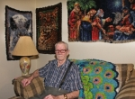 Bernard Woenker, of Huntington, sits in his living room surrounded by some of the latch hook rugs he has created. He estimates he has hooked as many as 300 rugs in the 40 to 50 years he has worked at his hobby.
