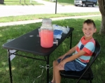 Bryden Ricker, 7, mans the lemonade stand at his home on Felt Street in Huntington Thursday, July 26. The youngster is donating the proceeds from his sales to benefit Riley Hospital for Children.
