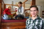 Nathan Park (right) stands next to the reading loft he built as a community service project for the children's book section of the Andrews-Dallas Township Public Library, as Emmalee Otto, 3, and her mother, Kari Otto, of Andrews, play on the Plexiglas-enclosed platform Saturday, Feb. 14.