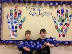 Jonas Bent (left) and Jayce Keyser, Lincoln Elementary School students, pose with their classroom's addition to the blue paper chain currently making its way around the school building.