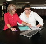 Credit recovery class teacher Leslie Nicola (left) helps senior Morgan Burkhart with her geography assignment on Thursday, Aug. 31, in the Huntington North High School's new Locker Lounge. Students can use the lounge to do homework, either individually or in groups.