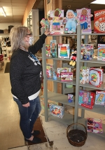 Mandy Riggers, manager of Covered with Love, Love INC's in-house thrift store, adjusts items on the shelf during the store's Family Day on Saturday, Dec. 19. Riggers and staff had to stop halfway through the sale and restock shelves because so many folks turned out for the event.