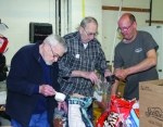 Volunteers (from left) Bob Gooley, Paul Vining and Jeremie Winkelman fill bags with dog food in the storage room of Love In the Name of Christ. The ministry will begin giving out a month's worth of groceries at a time to area residents in need of food.