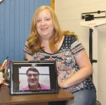 Kelley Miller, RN BSN, of Love In the Name of Christ, sits behind the desk of the ministry's telemetry clinic examination room in Huntington, as Dr. Brad Isbister is shown on the tablet in a live stream meeting used to make medical examinations from the Matthew 25 Health & Dental Clinic in Fort Wayne.