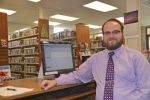 Nicholas Stephan sits at his desk in the Markle Public Library, where he is now serving as branch manager.