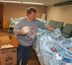 Volunteer Wanda Brosamer adds cereal to one of a sea of bags filled with food in the basement of Mission House Church in preparation for its food pantry distribution day in February. The ministry gives food to roughly 100 families per month.