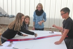 Parkview Huntington Boys & Girls Club members (from left to right) Natalee Searles, 9; Harlee Mason, 9; and Zander Mason, 11; receive guidance from LaFontaine Arts Council Artist-in-Residence Angela Ellsworth (third from left) as they paint a rainbow's stripes on a section of a mural at the club on Monday, Oct. 26. The mural will be displayed in downtown Huntington after it is finished.