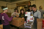 Huntington North High School New Tech students unpack boxes of microwave popcorn at Love In The Name of Christ, as part of a service component in their training program.