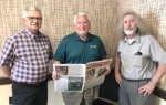 Don Hurd (middle), CEO of Hoosier Media Group, looks over an issue of The Huntington County TAB after he purchased the free newspaper from previous owners Russ Grindle (left) and Scott Trauner on Friday, June 19. The TAB is the 12th newspaper owned by Hoosier Media Group.