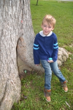 "Seven-year-old Noah Crittendon poses next to a painted rock he's hidden at the base of a tree in Hier's Park. Noah's mom, Ashley Crittendon, discovered the Kindness Rock Project while vacationing in Florida and spearheaded the organization of Huntington Indiana Rocks. The venture, she says, is meant to ""make people happy"" by painting and hiding rocks for others to find."