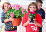 Boys and Girls Club of Huntington County members (from left) Brooklyn Holzinger, Sierrra White and Dylan Shively recently participated in a project to plant flowers in the downtown area planter boxes.