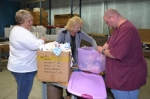 Material donated to Pathfinder Services' OutSource Manufacturing industrial wipes business is sorted by (from left) Kari Goetz, of Pathfinder Community Integration; Julie Parrett, sales for OutSource Manufacturing; and Brian Sommers.