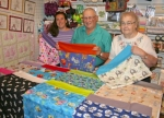 Nikki DeRose (left) is joined by Myron and Linda Ridgeway, of Huntington, as they display the various pillowcases Myron has sewn to donate to ConKerr Cancer.